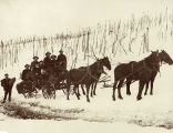 [Six men and a woman on horse-drawn coach in snow, one man standing beside.]