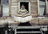 [Person in Chilkat blanket and spruce root hat in doorway, possibly Klukwan (PC).]