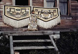 [Two Chilkat blankets and a tunic displayed in front of a house in Klukwan? (PC).]