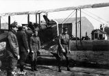 [L to R: two unidentified men, Capt. St. Clair Streett, Gen. Pershing in front of biplane.]