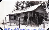 The log cabin; Mr. Elliott, Mr. Lutro, Mr. Rhymes & Mr. Baker [standing in front of log cabin].