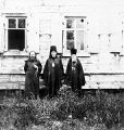 [Three Russian Orthodox priests standing in front of a wooden building.]