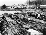 [Fort Wrangell military post; group of Alaska natives on rocks in foreground; waterfront of town...