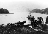 View from Fort Tongass; cannon in foreground; ship in harbor.]