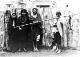 [Group of four Sitka Indians beside fence; one on right carrying a pole with a fish.]