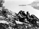 [Fort Wrangell from Rock Cod; group of people seated on ground in foreground.]
