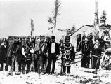 [Tlingit Indians at Wrangell or Tongass standing in front of totems and buildings.]