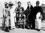 [Group of five people, standing, all in Tlingit (?) costume.]