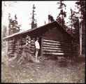 Man standing in doorway of log cabin.