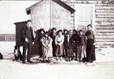 [Two adults with 8 native children in front of log building.]