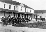 Ft. Gibbon, U.S. Army Signal Corp. men in uniform assembling in front of building - carrying gear...
