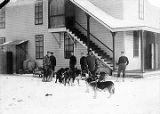 Ft. Gibbon.  U.S. Army Signal Corp. Men with dogs and sled in front of building.