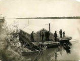 U.S. Army Signal Corp. Two men paddling canoes - others standing on barge along the shore.