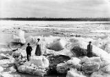 Two women and a man standing on large chunks of ice, as river breaks up.