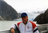 Frank Murkowski in an aluminum boat; glacier in the background.