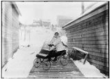 [Young girl steering four wheel pedal cart on boardwalk in winter.]