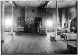 [Interior of barracks.  Cots, chairs, lamps, night stands, lockers, chests, musical instruments,...