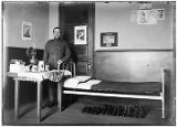 [Man in uniform (Sergeant) standing near cot and table, six pairs of shoes and boots under cot. ...