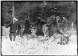 [Two hunters standing in snow near snow shoes and four bear skins.]