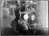 [Man sitting in kitchen area, pans and utensils hanging from wall, pies on table.]