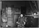 [Man in military uniform sitting in chair next to dresser, 22nd Infantry insignia on cap.]