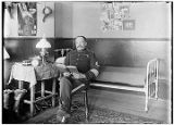 [Man in uniform (Sergeant) sitting in chair reading a book, cot and nightstand near.]