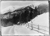 [Winter scene; snow covered road and wooden fence leading to shack, mountains in background.]