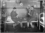 [Two men dressed in military uniforms sitting on cot playing cards, cornet on table and trombone...
