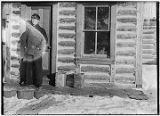 [Man standing in front of log cabin door.]