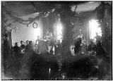 [Groups of men in uniform sitting at tables eating and drinking; room decorated for Christmas.]