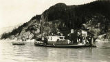 "[Another view of ""John.L.C.- Juneau"" [cannery tender-tug] towing a barge and a fishing boat."