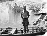[Bare chested man standing in boat in front of glacier. Kenneth Chisholm?]