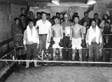 [Eskimo boxing match.  Ed Levin in white shirt; Chief Olaranna stands at center, holding board.]