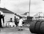 [Children and sailor on dock with houses in background.]