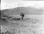[Man with pack crossing rocky flat land.]