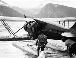 [3 men with floatplane, mountains in background.]