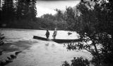 [View from behind foliage of two men on watercrafts, facing away from camera.]