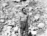 [Bare chested man in front of boulder strewn hillside.]