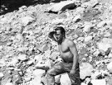 [Bare chested man in hip waiters posing in front of boulder strewn hillside.]