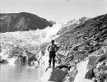 [Bare chested man standing on rocks near glacier.]