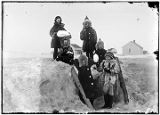 [Six children standing around snow fort, buildings in background.]
