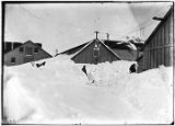 [Man making trail through deep snow.  Buildings and dog in background.]