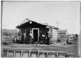 [Four men standing by log cabin, one man writing information on blackboard with N.C. Co. flag in...
