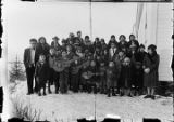[Group of children and adults standing outside of school next to ANB Hall, four children in front...