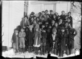 [Group of children and young adults standing outside of building in winter.]