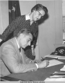 Governor Stepovich signs bill while Dora Sweeney watches, 1957.