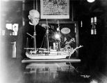 "[Andrew P. Kashevaroff and model of the Revenue Cutter ""Bear"" (ship) which is in..."