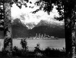 [World War I era armored cruiser framed by trees.]