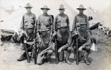 [Eight soldiers (four kneeling in front with rifles); Lt. Gerold E. Luebben is in the back row,...