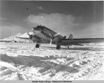 Douglas R4D cargo and passenger transport on snowy runway.